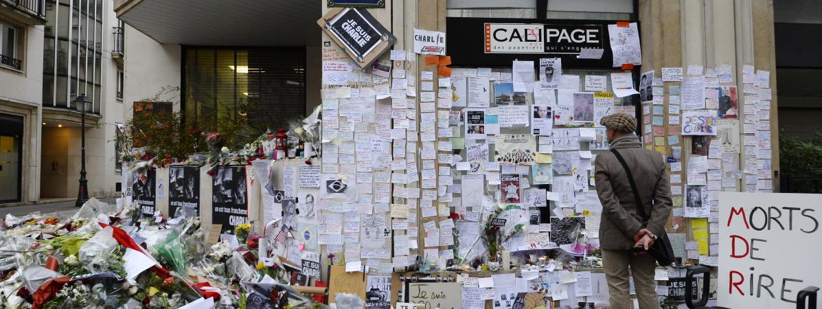 """Un homme se recueille devant un mémorial improvisé à proximité de l\'ancienne rédaction de \""""Charlie Hebdo\"""", à Paris, quelques jours après l\'attaque du 7 janvier 2015."""