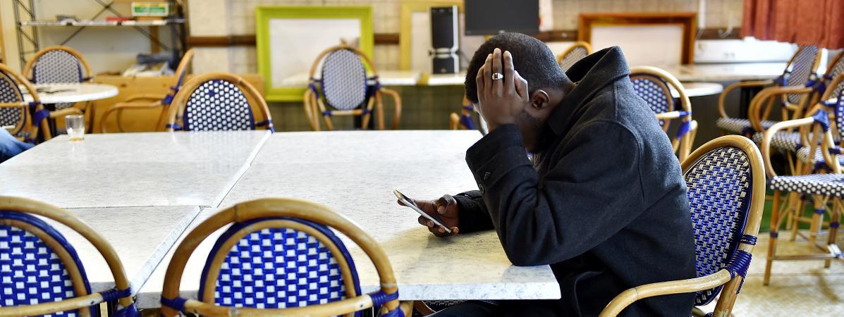 Un homme venu du Soudan consulte son téléphone portable dans un centre d\'accueil et d\'orientation pour migrants, à Saint-Brévin-les-Pins (Loire-Atlantique), le 4 janvier 2017.