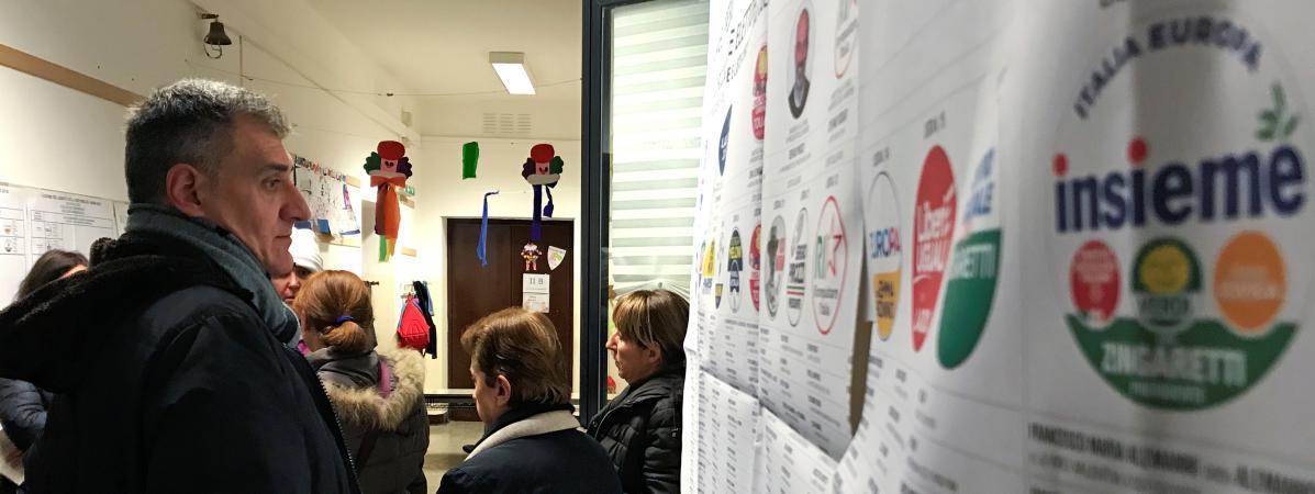 Un homme regarde les listes de vote dans un bureau électoral à Rome (Italie), le 4 mars 2018.