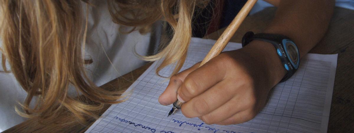 Une élève de CM2 écrit une dictée, en juin 2007.