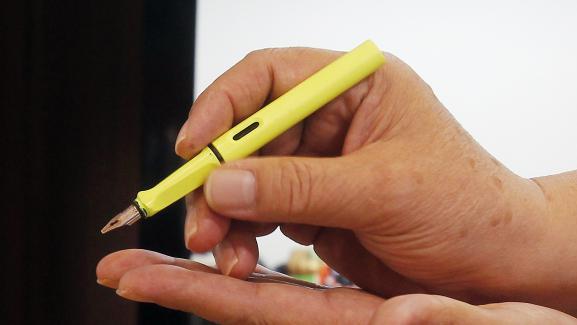 Voici labonne manière de tenir un stylo, ici présentée par le propriétaire d'un magasin de Taipei (Taïwan) à un client, le 24 mars 2017.
