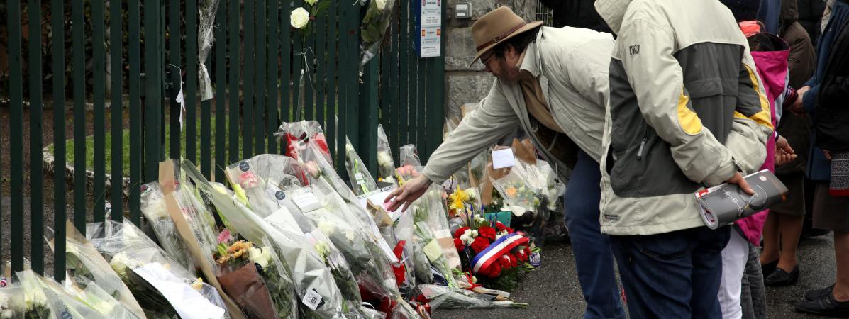 Des personnes viennent rendre hommage au gendarme Arnaud Beltrame, samedi 24 mars 2018 à Trèbes (Aude).