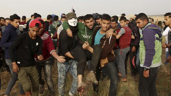 """Des Palestiniens évacuent un blessé lors de rassemblements qui ont suivi la \""""marche du retour\"""" dans la bande de Gaza, le 5 avril 2018."""