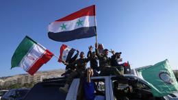 Des partisans du régime de Bachar al-Assad brandissent des drapeaux syrien, iranien et russes et chantent des slogans anti-Trump lors d\'une manifestation le 14 avril 2018. L\'Iran et la Russie ont dénoncé les opérations aériennes orchestrées par les Etats-Unis, la France et le Royaume-Uni.