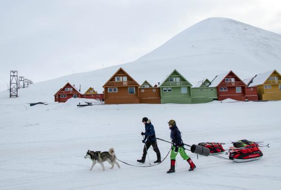 Un couple et son chien passent devant un lotissement au pied de la montagne Sukkertoppen, le 28 mars 2018, à Longyearbyen.