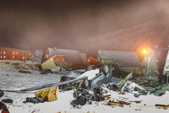 Une voiture renversée et des débris jonchent le sol enneigé, devant des maisons déplacées sur plusieurs dizaines de mètres, le 7 janvier 2016, à Longyearbyen, plus de deux semaines après une avalanche meurtrière.