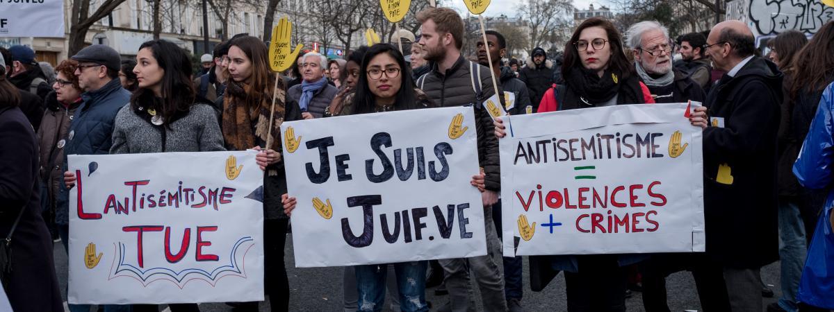 Des manifestants portent des pancartes dénonçant l\'antisémitisme, le 28 mars 2018, à Paris, pendant une marche blanche en hommage à Mireille Knoll, octogénaire juive tuée dans la capitale.