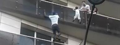 Mamoudou Gassamasauvant un enfant suspendu dans le vide, dans le 18e arrondissement de Paris, samedi 26 mai 2018.