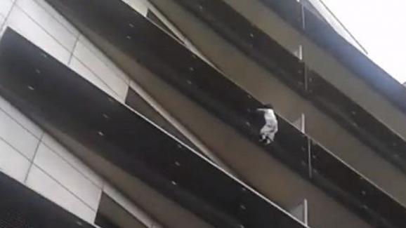 Sur cette capture d\'écran de la vidéo du sauvetage, on peut apercevoirle petit garçon s\'aider de ses pieds etdu grillage pour se maintenir.