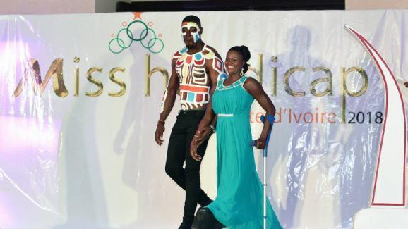 Accompagnée par un guide, une candidate malvoyante défile sur le podium lors du premier concours Miss handicap Côte d\'Ivoire en mai 2018.