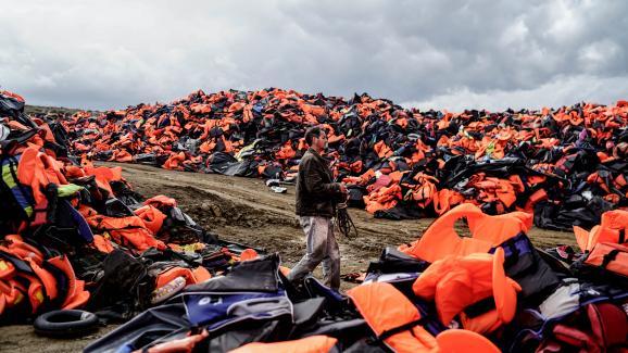 Un homme marche au milieu de gilets de sauvetage laissés par des migrants, après leur traversée de la mer Egée et leur arrivée sur l\'île grecque de Lesbos (Grèce), le 27 novembre 2015.