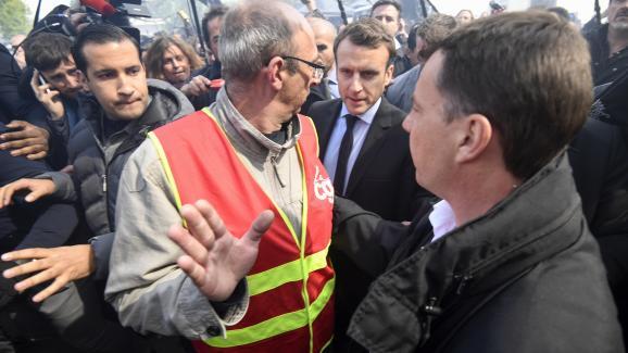 """Le 26 avril 2017, à l\'usine Whirlpool d\'Amiens (Somme) menacée de fermeture, Emmanuel Macron est accueilli par des huées etdes chants au son de \""""Marine, présidente !\"""". A ses côtés, Alexandre Benalla est là pour assurer sa sécurité."""