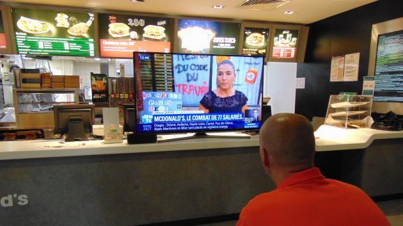 Un salarié regarde une chaîne d\'information en continu relayant le conflit social au McDonald\'s Saint-Barthélemy, le 9 août 2018 à Marseille (Bouches-du-Rhône).