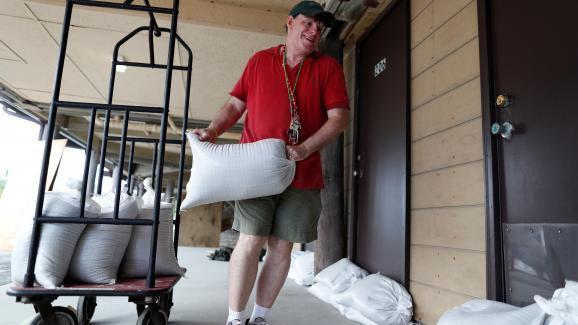 Un habitant deGarden City, en Caroline du Sud, aux Etats-Unis, dépose des sacs de sables devant des habitations, avant l\'arrivée de l\'ouragan Florence, le 11 septembre 2018.