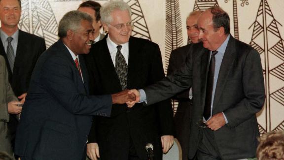 Le Premier ministre, Lionel Jospin (c), observe une poignée de mains entre l\'indépendantiste Roch Wamytan (g) et le non-indépendantiste Jacques Lafleur (d), le 5 juin 1998, après la signature d\'un accord à Nouméa (Nouvelle-Calédonie).