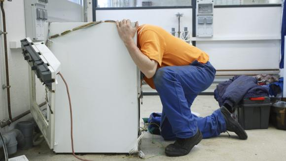 Un homme répare lui même son électroménager plutôt que d\'acheter du neuf.