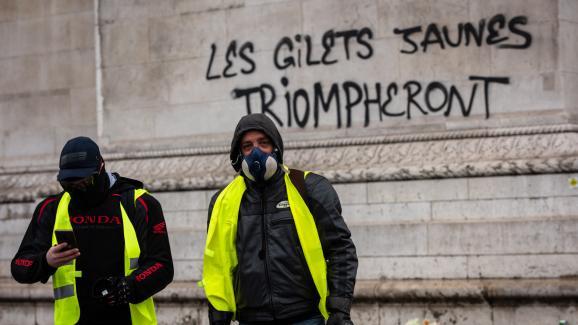"""Des \""""gilets jaunes\"""" manifestent sur la place de l\'Etoile à Paris, devantune inscription taguée sur l\'Arc de triomphe, le 1er décembre 2018."""