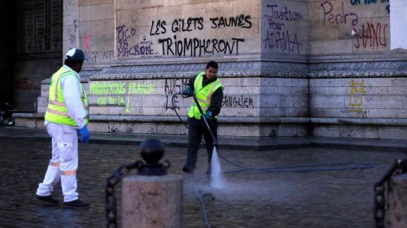 """Des agents de la ville de Paris nettoient l\'Arc de triomphe et ses abords, le 2 décembre 2018, au lendemain du rassemblement des \""""gilets jaunes\"""" sur la place de l\'Etoile."""