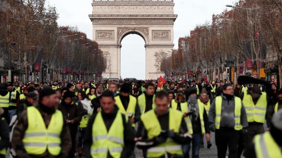 """Des \""""gilets jaunes\"""" descendent l\'avenue des Champs-Elysées, le 8 décembre 2018 à Paris."""