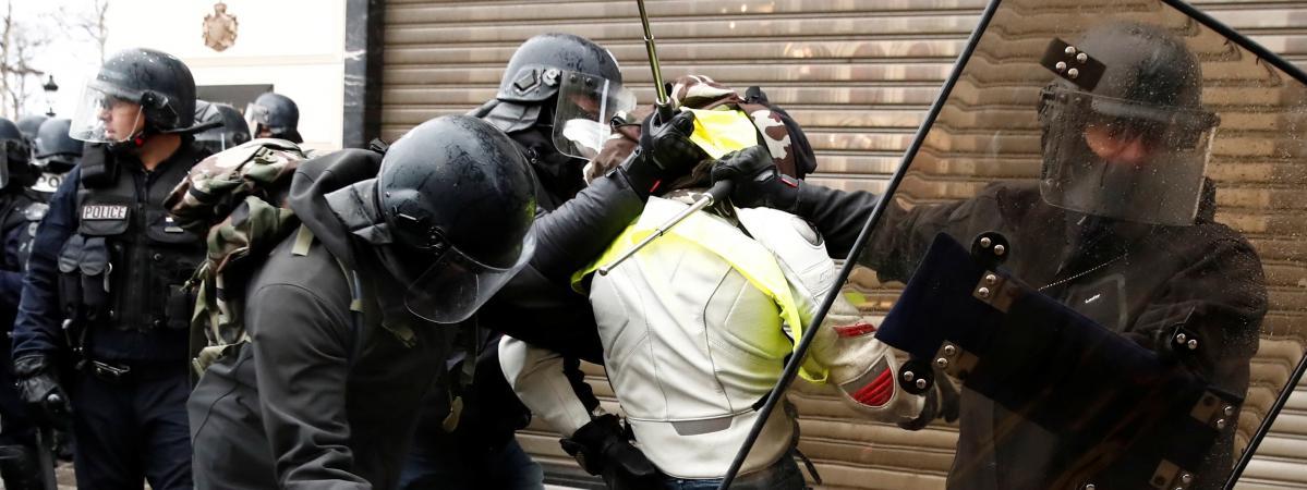"""Des policiers appréhendent un manifestant en marge de la mobilisation des \""""gilets jaunes\"""" à Paris, le 8 décembre 2018."""