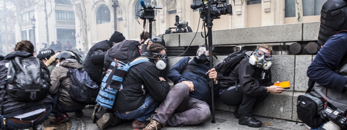 """Des journalistes se mettent à terre pour éviter les tirs de flash-balls lors de la mobilisation des """"gilets jaunes"""" à Paris, le 8 décembre 2018."""