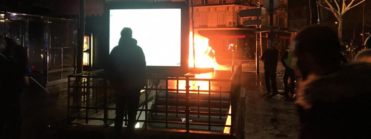"""Une voiture brûlée place du Trocadéro à Paris en marge d'un rassemblement des \""""gilets jaunes\""""."""