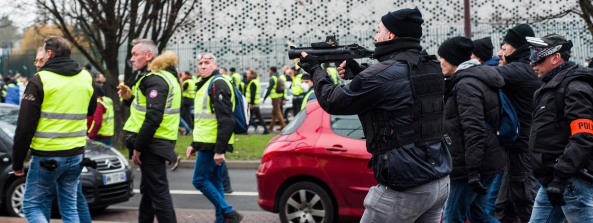 """Un policier de la brigade anticriminalité pointe unflash-ballen direction de """"gilets jaunes"""", le 29 décembre 2018, à Lille, lors d'une manifestation."""