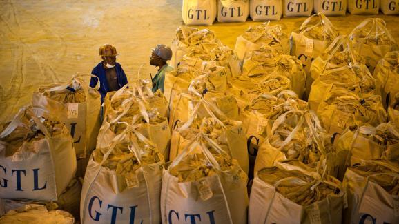 Deux ouvriers parlent à côté de sacs de cobalt dans une usine de retraitement de Lubumbashi.