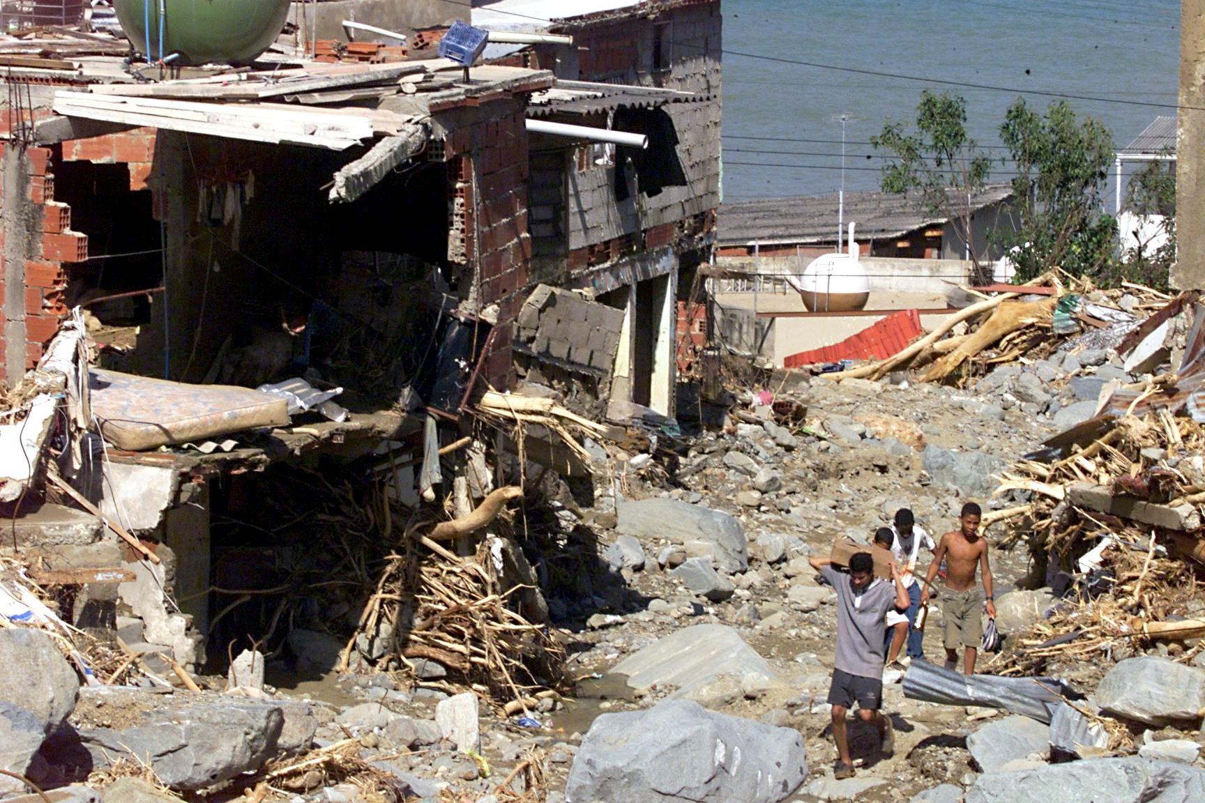 Des habitants marchent parmi les débris à La Guaria (Venezuela) le 19 décembre 1999 après d\'importantes inondations.