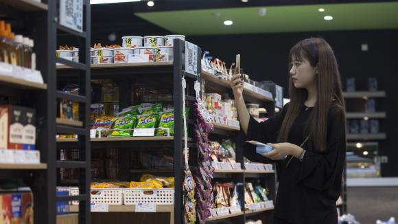 Une consommatrice scanne un produit pour le payer dans un magasin à Hangzhou