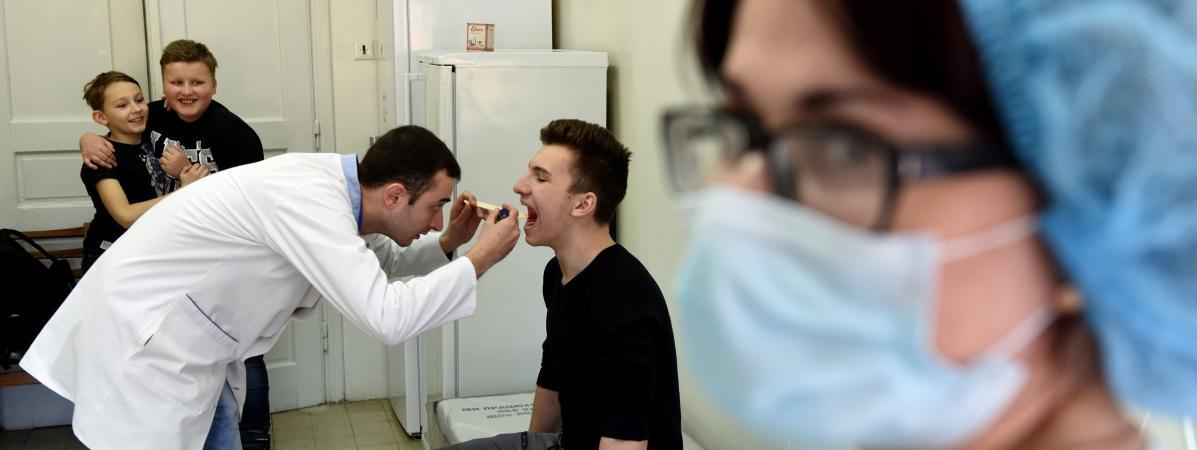 Un médecin examine un adolescent avant une vaccination contre la rougeole, le 19 février 2019 à Lviv (Ukraine).