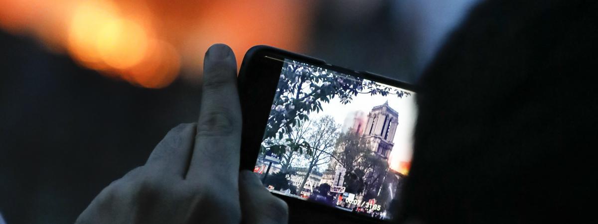 Un homme photographie la cathédrale Notre-Dame de Paris en feu, le 15 avril 2019.