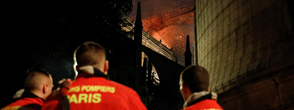 Des pompiers observent l\'incendie qui ravage la toiture de la cathédrale Notre-Dame de Paris, le 15 avril 2019.