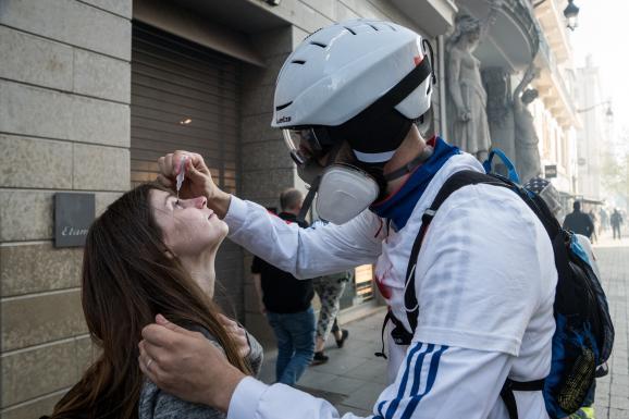 """Un \""""street medic\"""" met du sérumphysiologique dans les yeux d\'une femme, lors d\'une manifestation des \""""gilets jaunes\"""", le 23 mars 2019 à Lyon."""
