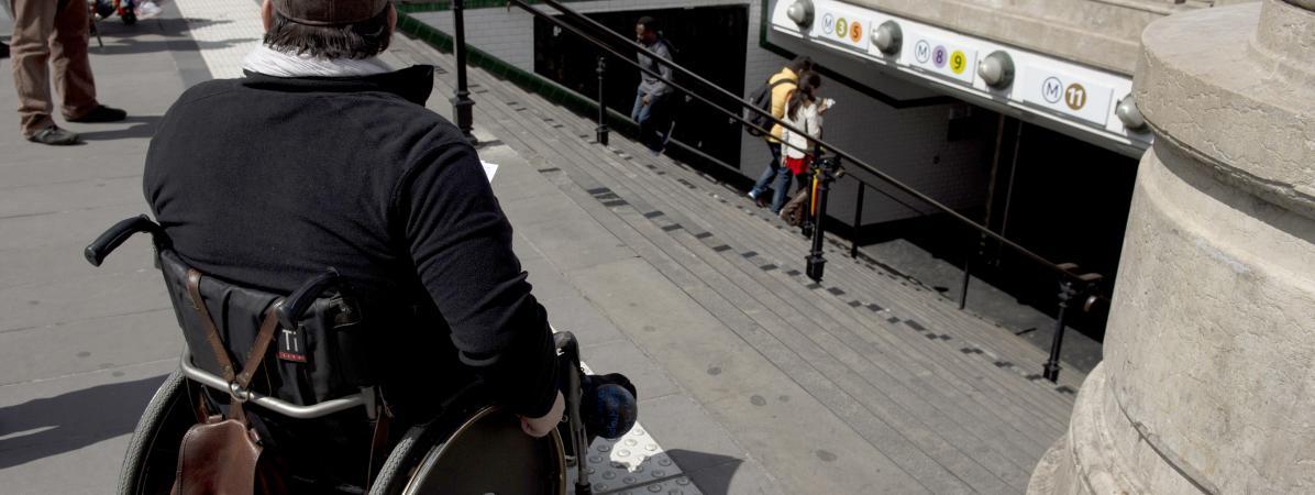 Un homme en fauteuil roulant en haut des escaliers d'une station de métro, le 13 mai 2014 à Paris.