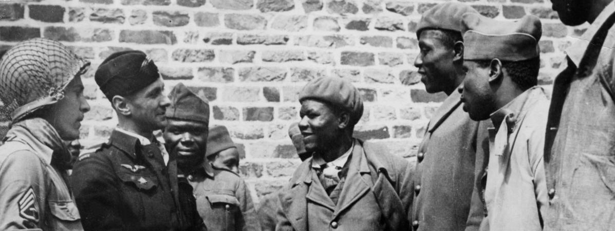 """Fin juillet 1944 en Normandie : des soldats francaisvenus d\'Afrique, capturés par les Allemands en 1940 et qui viennent d\'être libérés de leur \""""Frontstalag\"""", discutent avec un soldat de la VIIe US Army et un officier aviateur francais."""