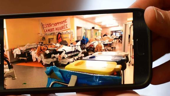 Un membre du personnel de l\'hôpital de Lons-le-Saunier (Jura) montre une photo de l\'engorgement des urgences, lors d\'un mouvement de grève le 21 janvier 2019.