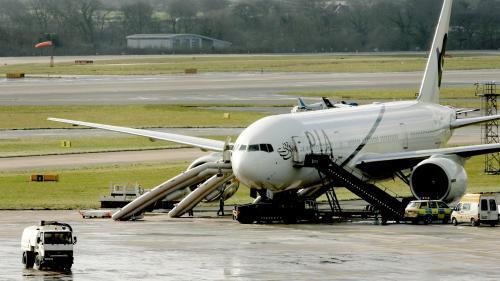 A bord d'un avion prêt à décoller, une passagère veut aller aux WC, mais ouvre la porte de l'issue de secours par mégarde