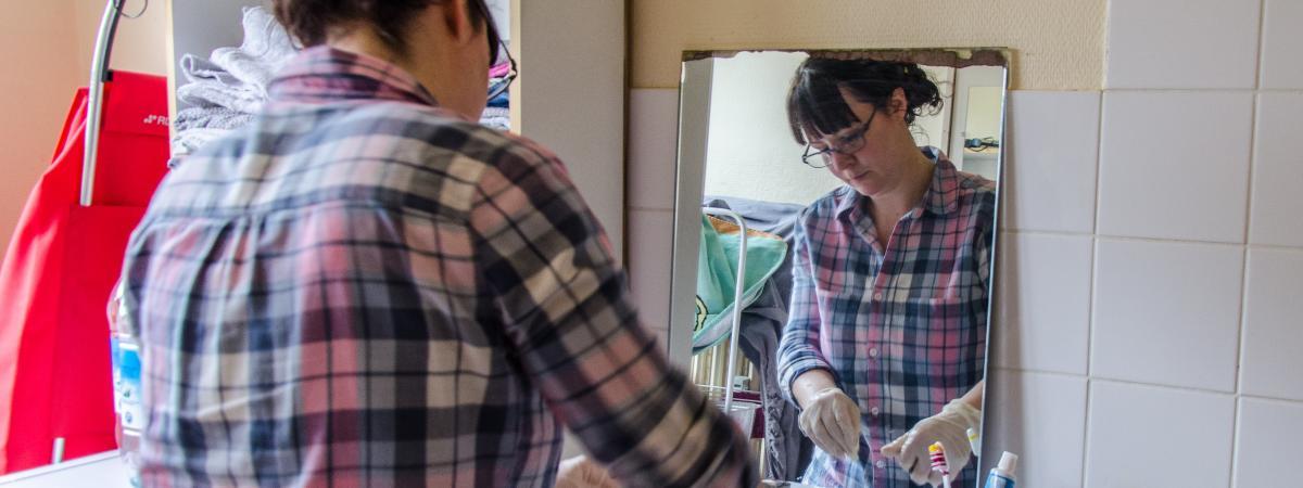 Laura Léon nettoie la salle de bain d'une personne dont elle s'occupe, le 17 mai 2019, à La Ferté-Bernard (Sarthe).