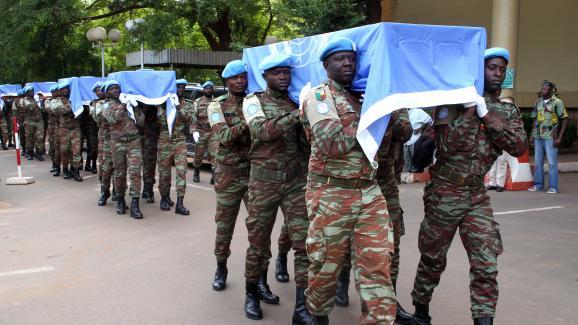 Des soldats nigériens de la Minusma portent les cercueilsaux couleurs de l\'ONUde neufs soldats à Bamako, le 7 octobre 2014.