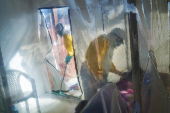 Des acteurs de santé, munis de combinaisons de protection, s\'occupent d\'une personne atteinte d\'Ebola, placée dans un cube d\'isolation à Beni (nord-est de la RDC) le 13 juillet 2019.