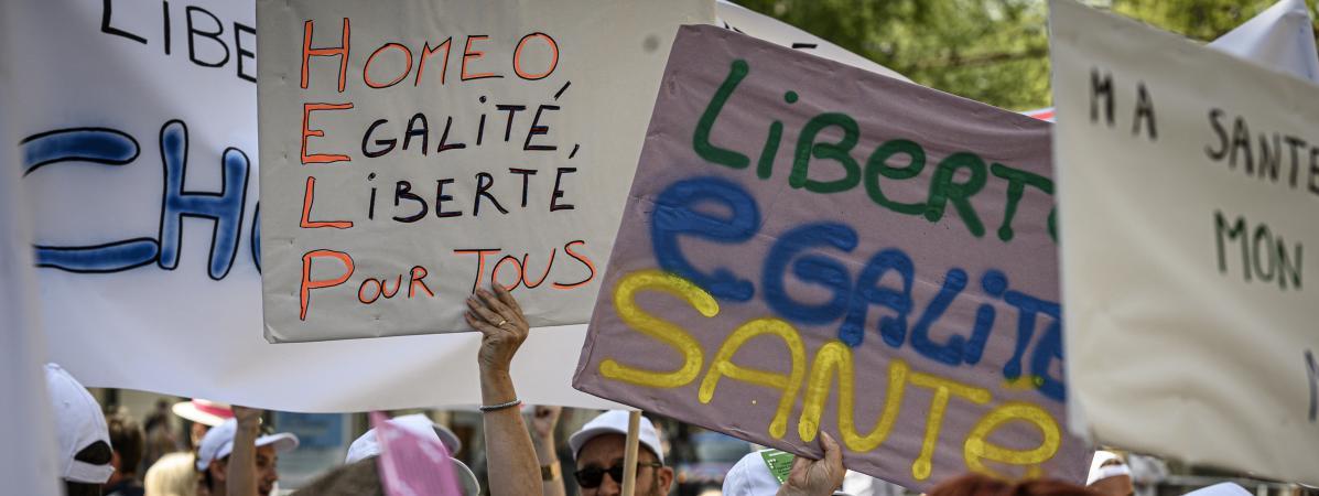 Des pancartes brandies lors d'un rassemblement en faveur de l'homéopathie, le 28 juin 2019 à Lyon.   JEAN-PHILIPPE KSIAZEK / AFP