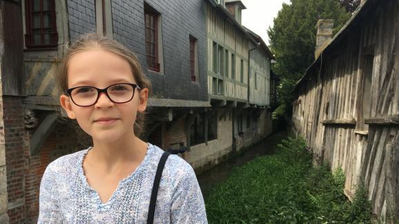 """Margot, dix ans, devant un petit pont, à Pont L\'Evêque, qu\'elle trouve \""""très mignon\""""."""