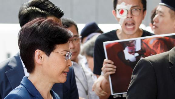 La cheffe du pouvoir exécutif de Hong Kong, Carrie Lam, passe devant des manifestants, devant son bureau, à Hong Kong, le 13 août 2019.