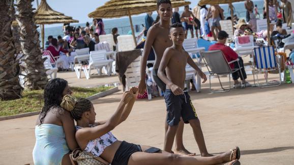 Des garçons marocains regardent des filles bronzer à la nouvelle piscine publique de la capitale Rabat, le 7 août 2019.