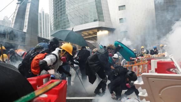 Des manifestants essuient des tirs de gaz lacrymogène de la police à Hong Kong, le 25 août 2019.