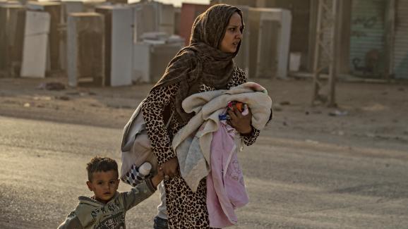 Une femme kurde et son fils fuient le village de Ras al-Aïn, le 9 octobre 2019, alors que les premières frappes turques commencent.