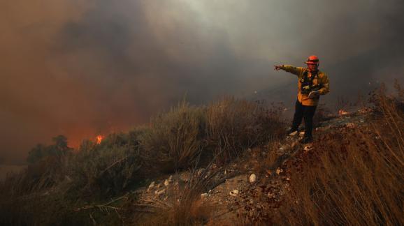 """Un pompier surveille la progression du \""""Tick Fire\"""" à Canyon Country, en Californie (Etats-Unis), le 24 octobre 2019."""