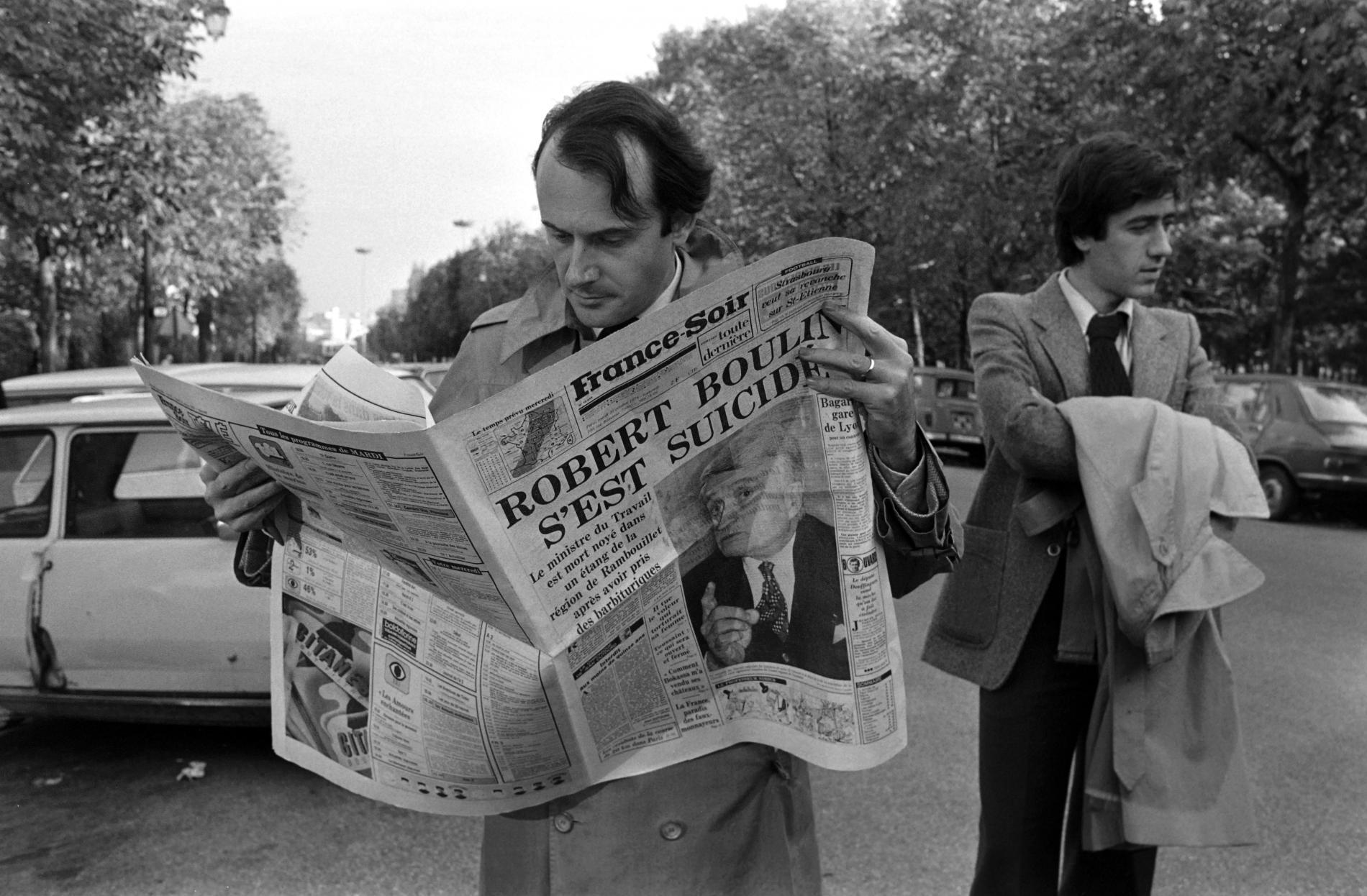 """Un homme lit le journal \""""France Soir\"""", à Paris, le 30 octobre 1979, jour de l\'annonce de la mort de Robert Boulin."""