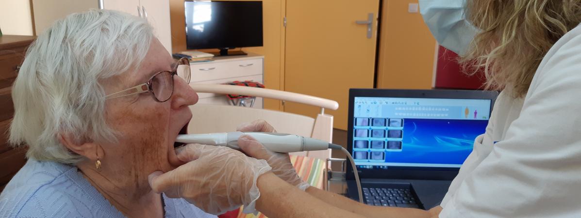 L'infirmière Yvette Bordas filme la dentition d'Anne-Marie, résidente à l'Ehpad de Sancerre. Le film et les photos sont ensuite analysés par un dentiste, à l'hôpital de Bourges. | SOLENNE LE HEN / RADIO FRANCE